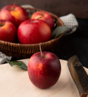Side view red apples in a basket with an apple and a knife on the board