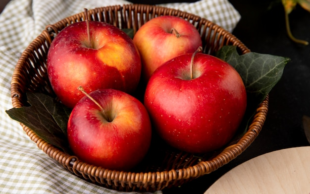 Side view red apples in a basket