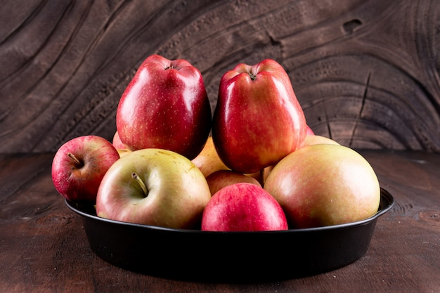 Side view red apples in black metal tray
