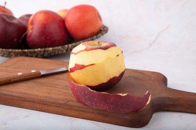 Side view red apples and knife with peeled apple on a board