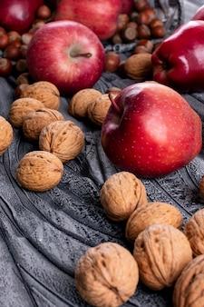 Вид сбоку красные яблоки с орехами и грецкими орехами на сером
