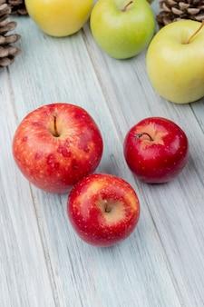 Vista laterale delle mele rosse con quelle gialle e verdi e pigne su fondo di legno