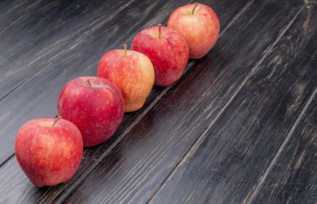 Vista laterale delle mele rosse su superficie di legno con lo spazio della copia