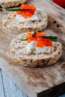 Вид сбоку закуска из красной икры хрустящие хрустящие хлебцы с творогом красная икра тархун и черный перец на доске