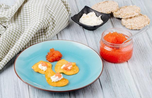サイドビュー赤キャビアの前菜ポテトチップスとクリームカッテージチーズ赤キャビアとカリカリのクリスプブレッド白い木製のテーブル