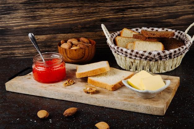 Vaso di caviale rosso vista laterale con bianco e pane di segale burro di mandorle e noci su una tavola