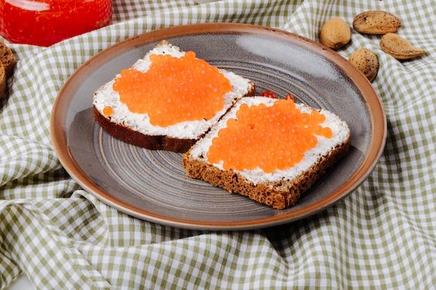 Vista laterale caviale rosso toast pane di segale con ricotta caviale rosso e mandorle sul tavolo