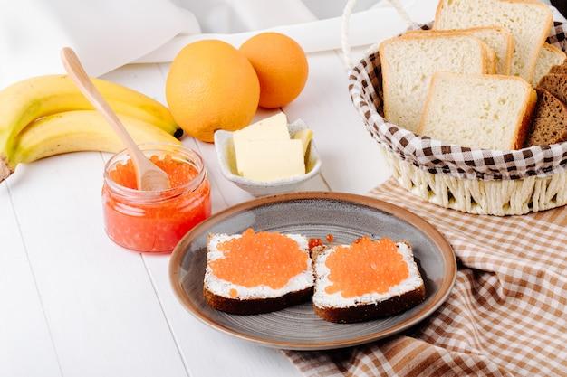 Вид сбоку красная икра тост ржаной хлеб с творогом красная икра сливочное масло белый хлеб апельсин и банан на белом столе