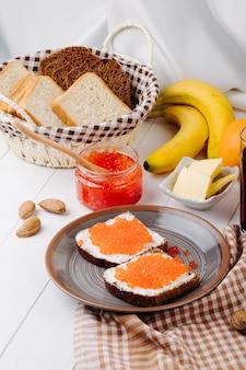 Вид сбоку красная икра тост ржаной хлеб с творогом красная икра сливочное масло белый хлеб апельсин банан и миндаль на столе