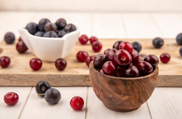 Side view of red cherries on a wooden bowl with dark purple sloes on a white bowl on a wooden kitchen board on a white wooden background