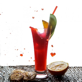 Side view red fruit smoothie with tubules for beverages and half orange and drops in serving napkins