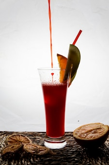 飲料用の尿細管とドライレモンのナプキンのサービングのドロップと赤い果実のスムージーの側面図