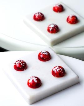 ミラーイメージの白いスタンドに白い斑点のあるチョコレート菓子で赤い側面図