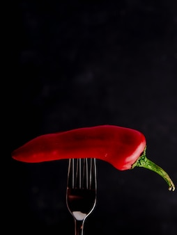 Side view of red pepper on fork on black background with copy space