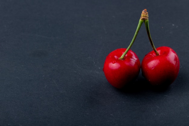 Side view of red ripe cherry isolated on black with copy space