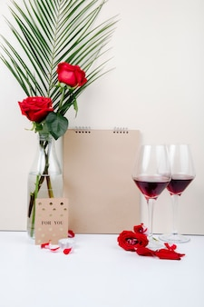 Side view of red roses with palm leaf in a glass bottle standing near a sketchbook and two glasses of red wine on white background