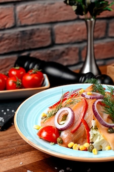 Салат из красной копченой рыбы с луком, кукурузой и помидорами