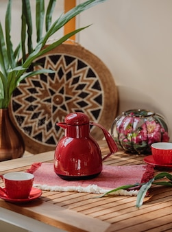 Side view of red tea set of cups and teapot on a wooden table