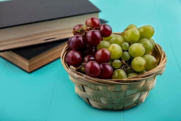 Side view of red and white grapes in basket with closed books on blue background
