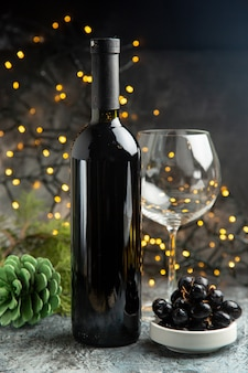 Side view of red wine bottle for celebration an empty glass and a black grape conifer cone on dark background