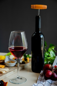 Side view of red wine bottle with corkscrew and different kinds of cheese olive walnut grape on white surface and black background