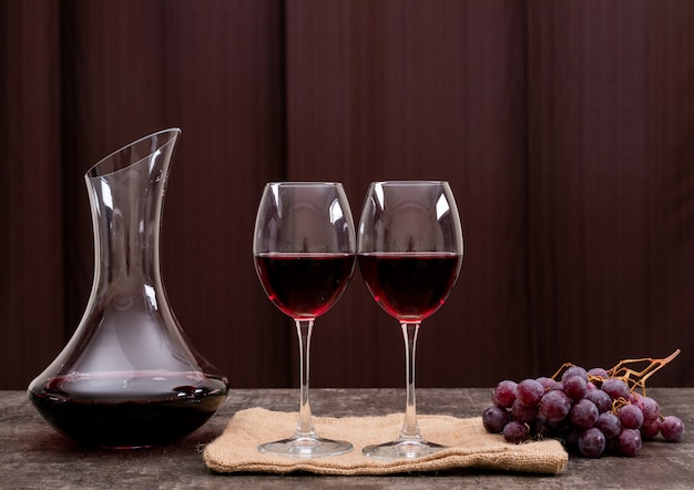 Side view red wine in glass with grape on horizontal