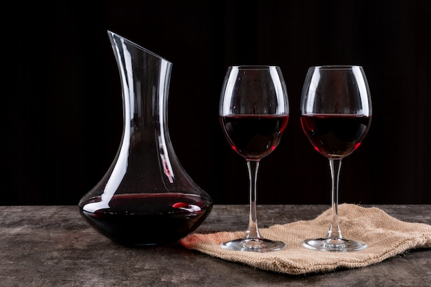 Side view red wine in glasses and linen cloth on dark horizontal