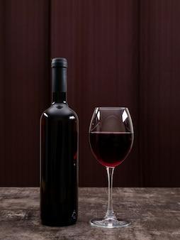Вид сбоку красное вино в бутылке с бокалом на вертикали
