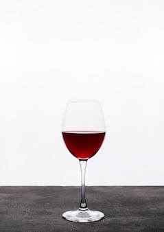 Вид сбоку красное вино в бокале на белой вертикали
