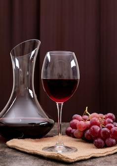 Вид сбоку красное вино в бокале с виноградом на вертикали
