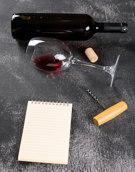 垂直の黒い石のノートにコピースペースを持つ側面図赤ワイン