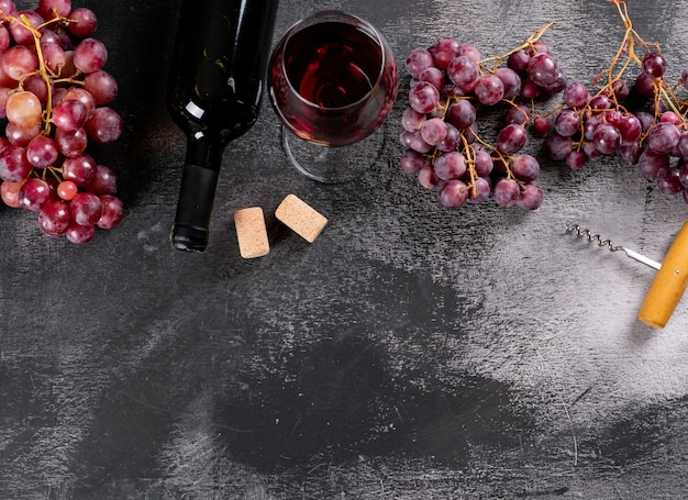 Вид сбоку красное вино с виноградом и копией пространства на черном камне по горизонтали
