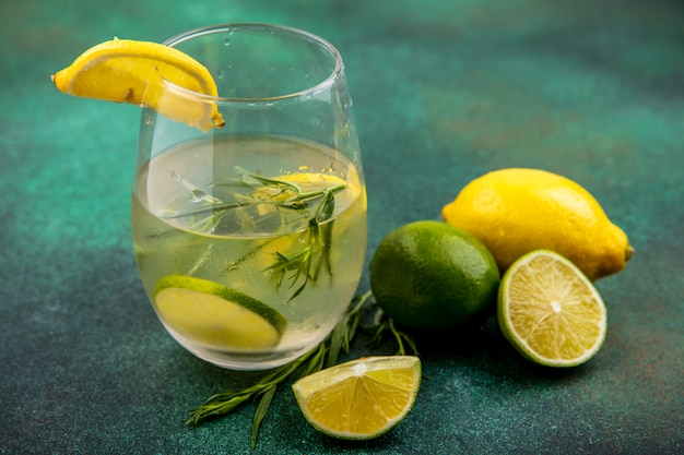 Side view of refreshing detox water in a glass on a wooden kitchen board with slices of lime and lemons and cinnamon sticks on green