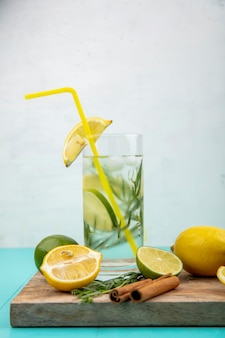 Side view of refreshing summer detox water with yellow lemon on white
