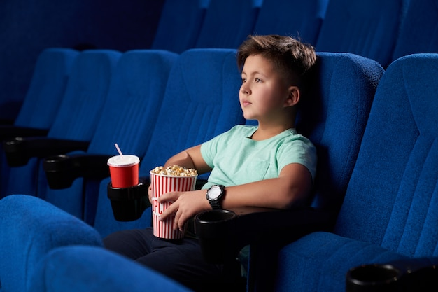 Side view of relaxed male teen eating junk food in cinema