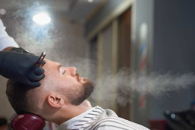 Side view of relaxed man getting haircut in barber shop