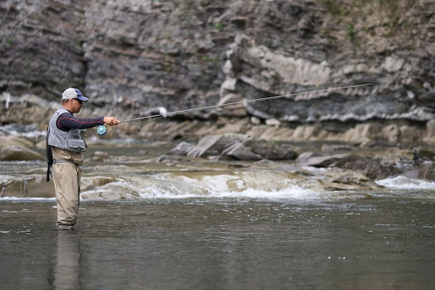 Side view of relaxed man in waterproof clothing standing motionless in river while fishing. mountain nature. concept of active lifestyle.