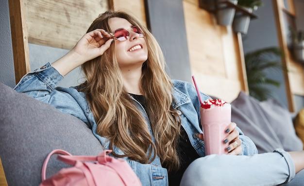 Vista laterale della ragazza alla moda rilassata che si siede nella caffetteria in occhiali da sole,