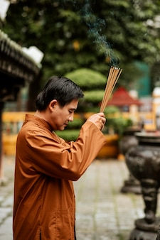 Side view of religious man at the temple with incense