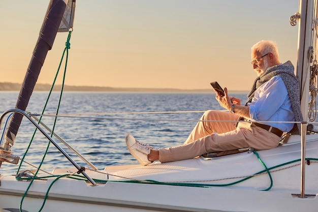Side view of a retired man sitting on the side of his sailboat or yacht floating in the calm blue