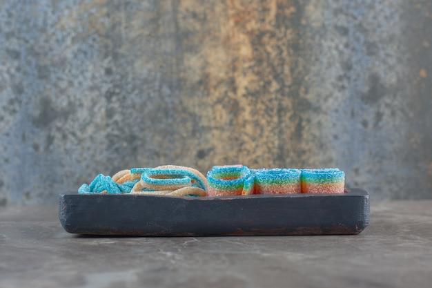 Vista laterale di caramelle a nastro su tavola di legno.