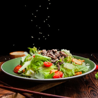 Side view rice pouring on delicious salad meal in plate with chopsticks on wooden and black background. space for text