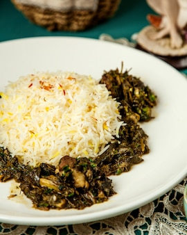 Side view of rice with stewed meat and herbs in white plate