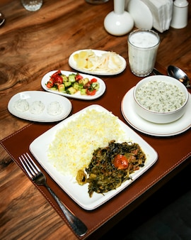 Side view of rice with stewed meat and herbs on wooden table