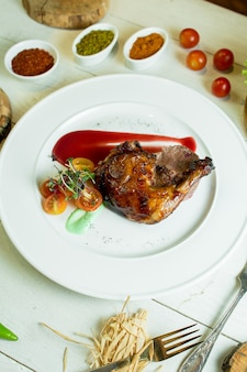 Side view of roast chicken leg with cherry tomatoes and ketchup on white plate