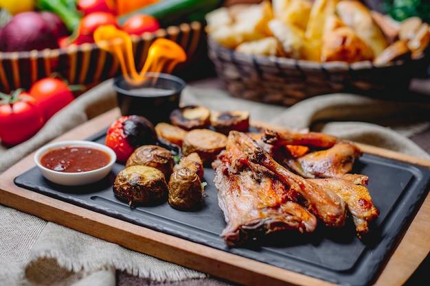 La vista laterale del pollo arrostito con le patate al forno ha grigliato le verdure e la salsa su un bordo nero