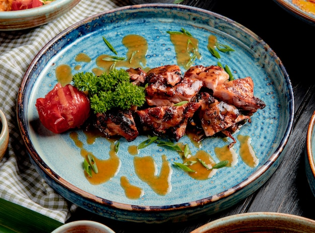 Side view of roasted chicken with grilled tomato fresh herbs and sauce on a plate on wood