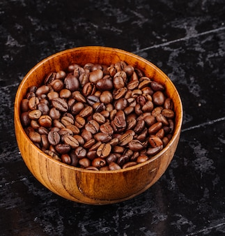 Side view of roasted coffee beans in a wooden bowl on black surface