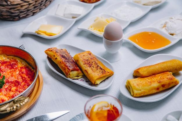 Frittelle rotolate vista laterale con uovo sodo e miele sul tavolo servito colazione