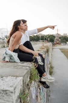 Vista laterale della coppia romantica che punta e che ammira la vista